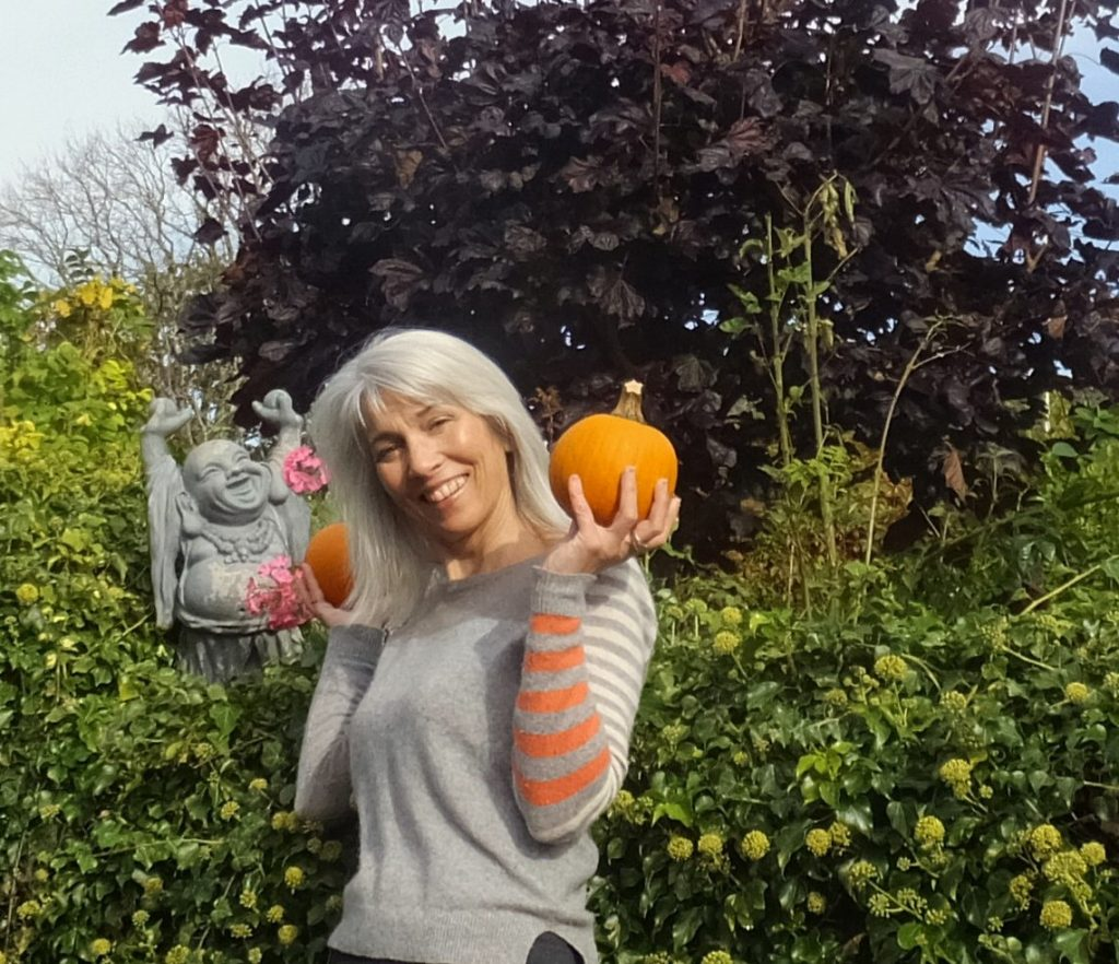Lady in grey sweater holding a baby pumpkin