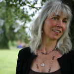 mature woman standing in garden with white hair