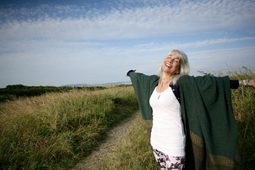 Summer grasses-woman in white and green shawl- smiling- arms open wide